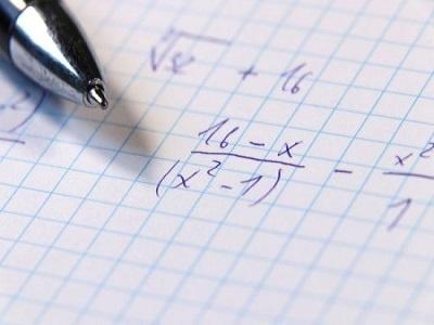 des calculs sur une page avec une plume a cote