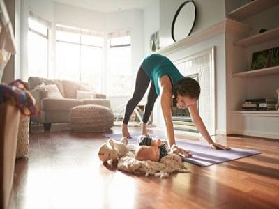 Une femme faisant de l'exercise dans son salon avec son bebe alonge a cote
